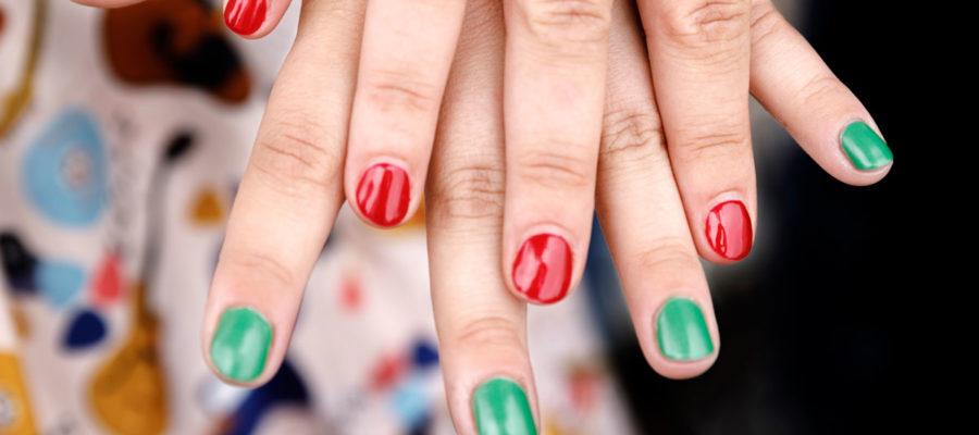 To hænder med rød og grøn neglelak.